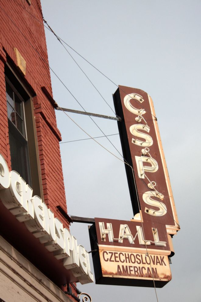 The sign for the hall hangs along West 7th Street.