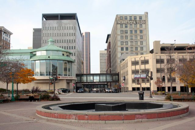 Turning to the north, the view is Cedar Street toward the Capitol grounds. Buildings on the left side of Cedar include the Crowne Plaza Hotel banquet room and behind it, the Degree of Honor building. A parking ramp and the Minnesota Building are on the right side of Cedar. The fountain in front (drained in preparation for the cold weather) is one of a pair in Kellogg Mall Park.