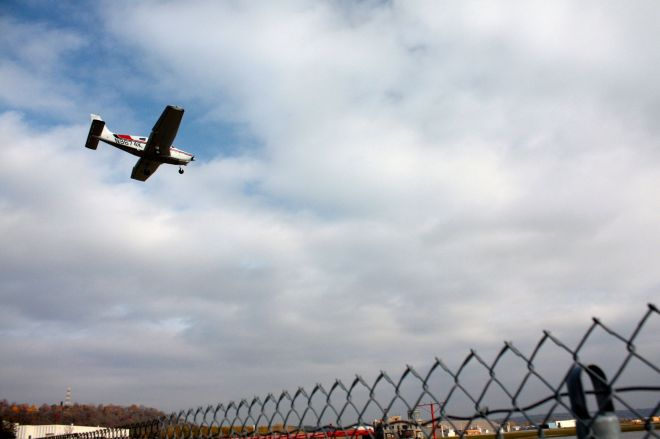 A single engine prop plane in its final approach to Holman Field. The fence in the forground keeps unwanted people and things off runways.