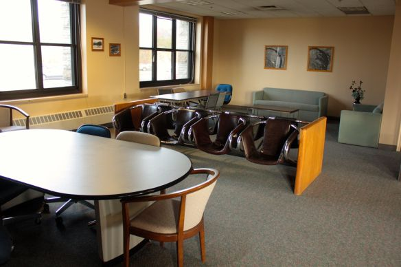 The small waiting area features a collection of unmatched furniture.