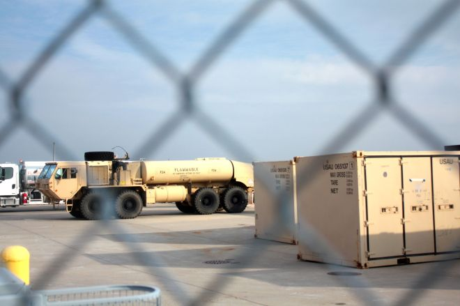 A National Guard fuel truck and storage lockers sit on the tarmac.