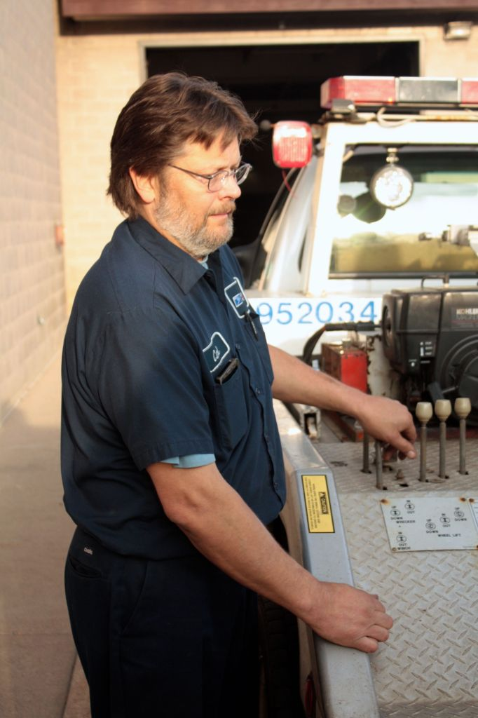 Karl Loberg lowers a mail vehicle he hauled in on his tow truck.