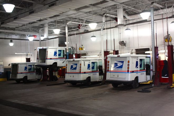 Four LLVs (Long-Life Vehicles) sit on lifts at the Riverview Vehicle Maintenance Facility.