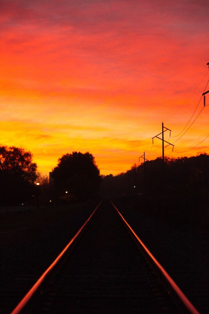 The railroad tracks immediately north of Grace Street at Oneida Street reflect the brilliant orange, yellow and purple cast by the sky.