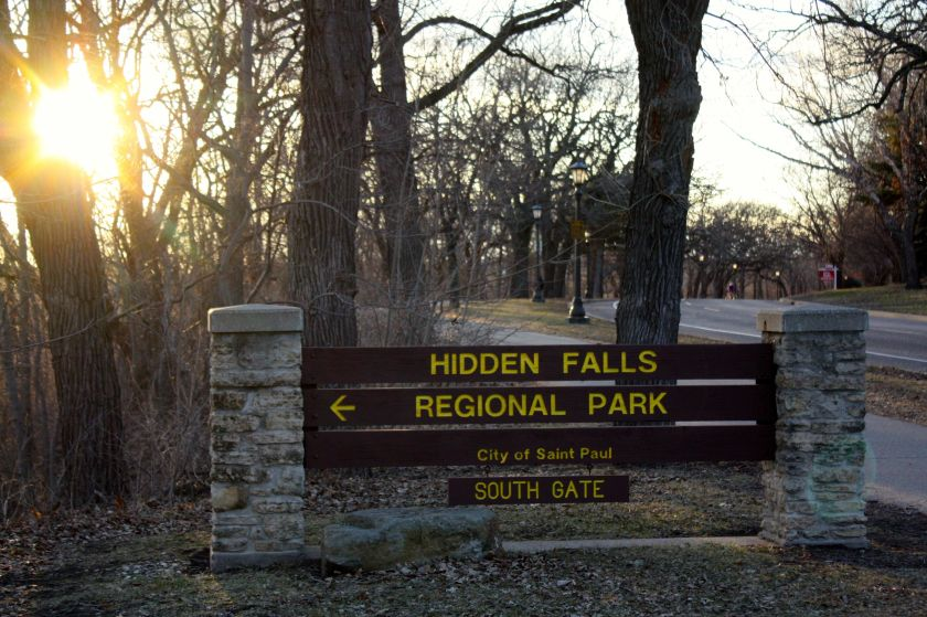 The sun hovers above the horizon as viewed from the Hidden Falls Park entrance.