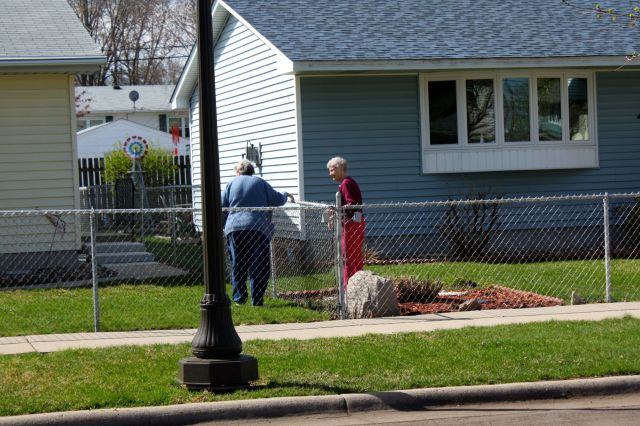 In a scene reminiscent of a Norman Rockwell painting, neighbors chat over the fence.