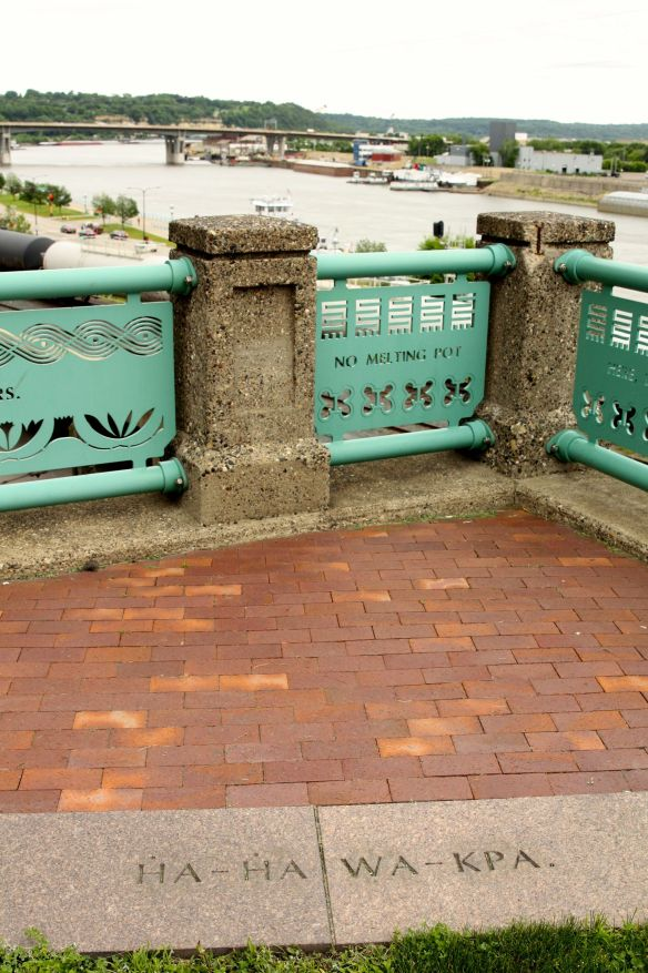 The Dakota word for Mississippi River(6), Ha-ha wa-kpa (literally 'river of the falls'), is carved into granite blocks, images representing the Mississippi and native plants, are in the fence and the Mississippi itself flows in the background.