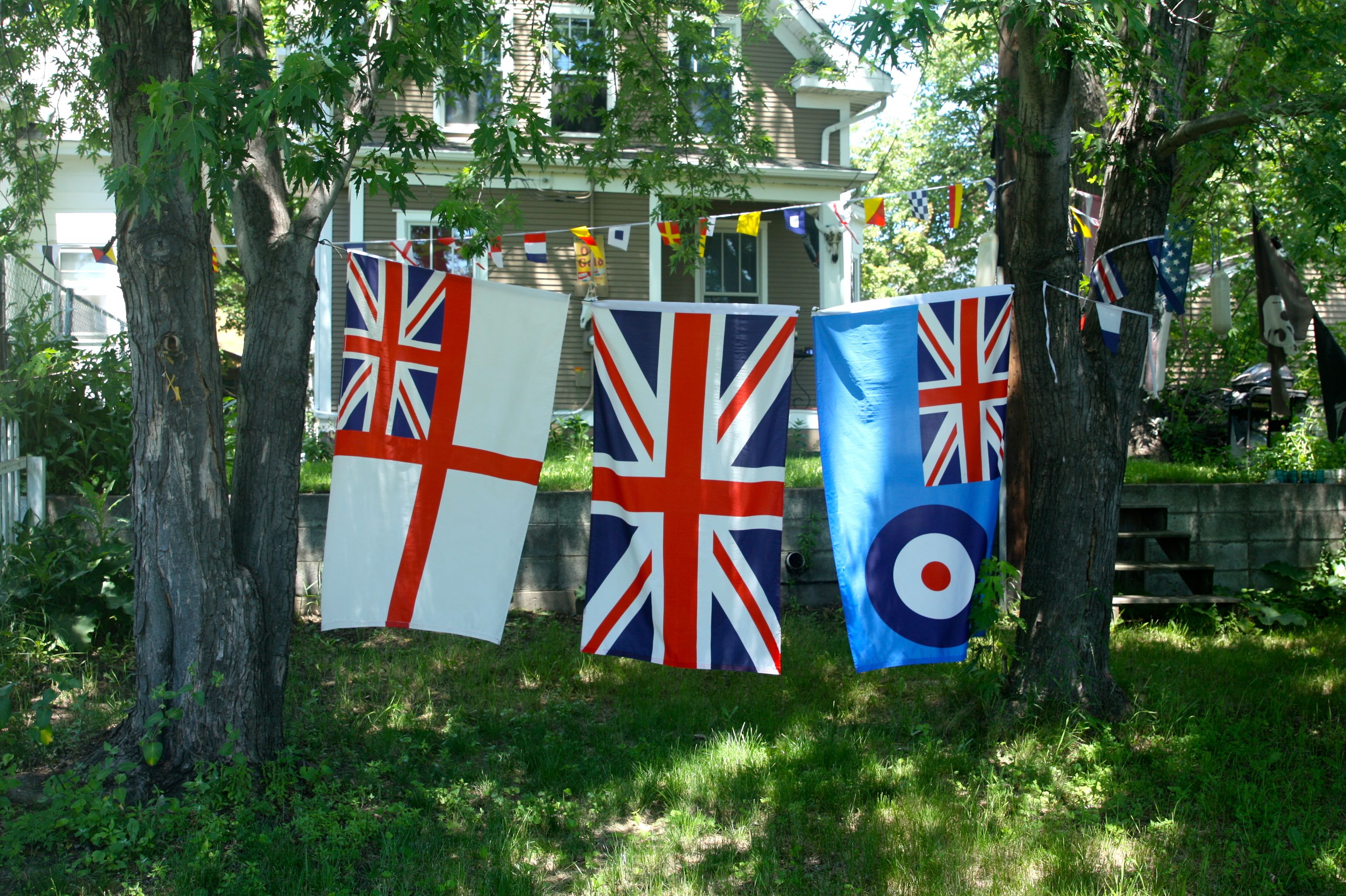 """The three flags, left to right, are the United Kingdom Naval Ensign """"White Ensign"""", the flag of the United Kingdom and Dhekelia, and the United Kingdom Royal Air Force Ensign flag."""