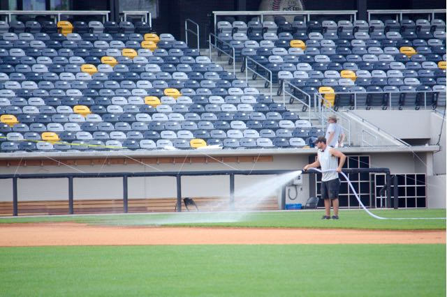A member of the grounds crew waters the infield grass.