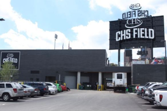 This is the back, or east, side of CHS Field. Parking here is primarily for those doing business with the Saints. The CHS Field sign to the right is the back of the scoreboard. The Pointe and Galtier Plaza, two of the areas tallest residential buildings, are visible under the scoreboard.