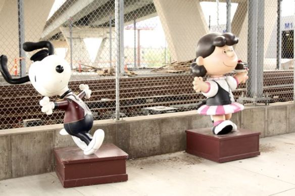 Snoopy and Lucy are two of several of the Peanuts gang on display on 4th Street, just east of CHS Field. The cyclone fence keeps the curious and miscreant away from the Green Line tracks and maintenance facility. The two large structures beyond the tracks are supports for the Lafayette Freeway Bridge.