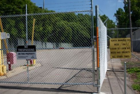 This Metro Council facility, its purpose not easily determinable, is protected by the tall fence topped with barbed wire.