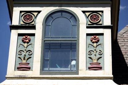 The arched window on the left and it's decorations are among the noticeable features of the asymmetrical second floor.