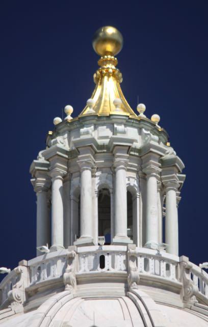 The peak of the Capitol dome glistens in the summer sun.