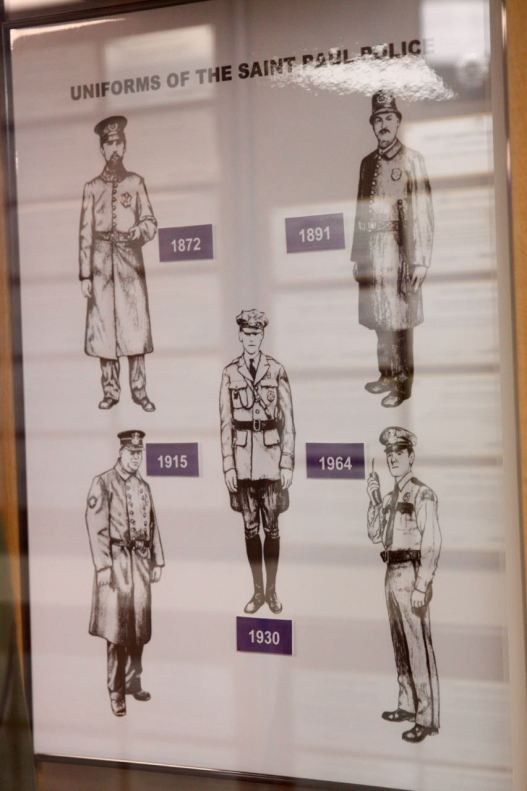 Police in Saint Paul have worn only five uniform designs since 1872 when the first set was introduced. This drawing of the history of the department's attire hangs in the museum.