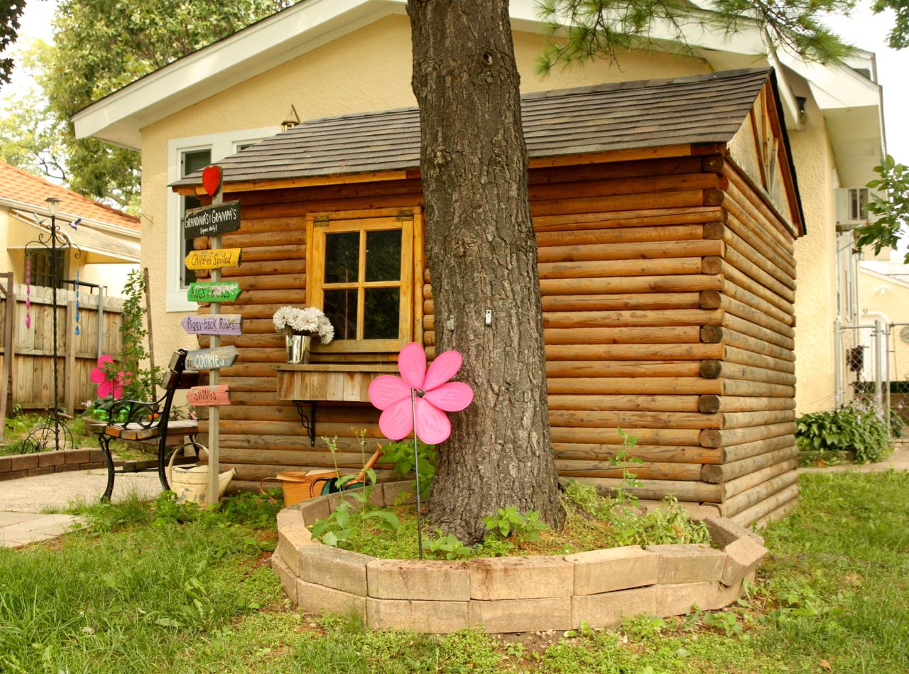 This log playhouse has working windows.
