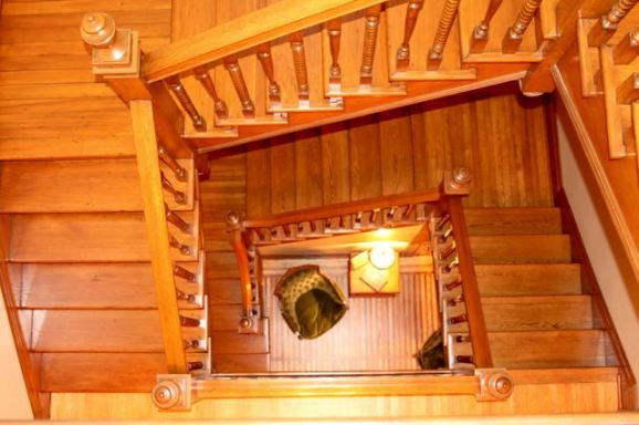 The view of the stairs and a portion of the sitting room looking down from the third floor. Dick stripped white paint off ALL of the woodwork in the picture.