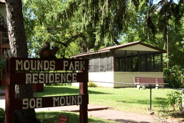 The corner of the Mounds Park Residence, behind the sign, and a portion of the grounds.