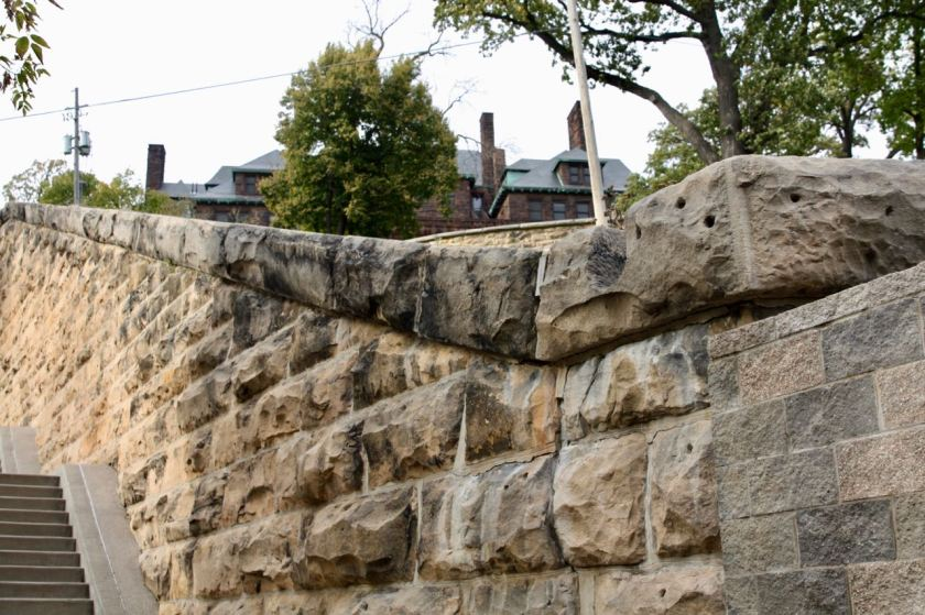 The two upper stories of the James J. Hill House are visible over the stone fence.