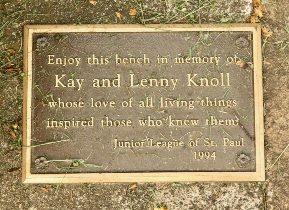 A memorial plaque, next to a different bench in the same area.