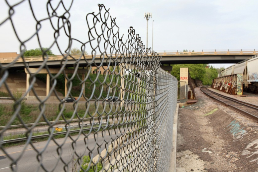 Interstate 94 goes past the north side of the railroad tracks, on the other side of the fence. Lightly traveled St. Anthony Avenue and brush border the south side of the tracks.