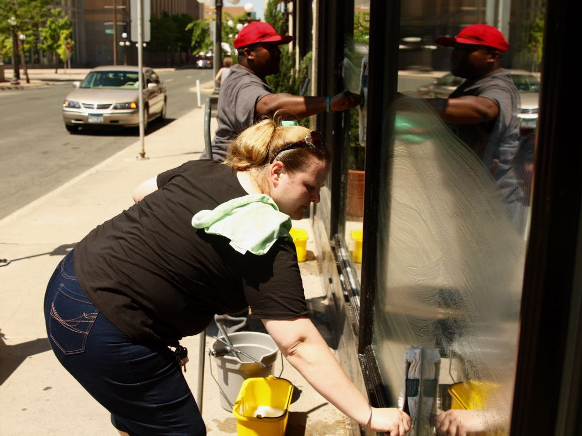 Kristina Schulte, foreground, and Jeff, her assistant, clean a store window along St. Peter Street in the Hamm Building.