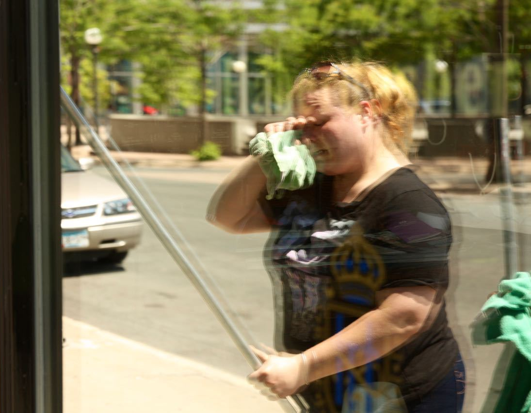 Kristina, reflected in a freshly cleaned window, wipes sweat off her face. 80 was the high temperature for May 21, 2016.