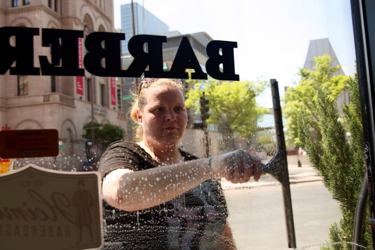 Kristina concentrates on cleaning the window.