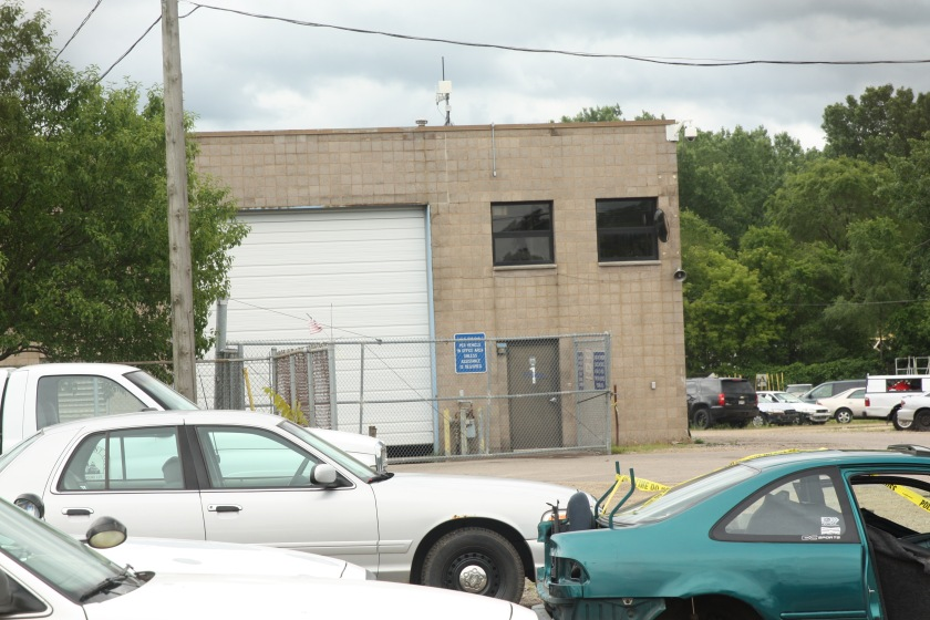 The impound lot office, like the lot itself, is protected by fencing.
