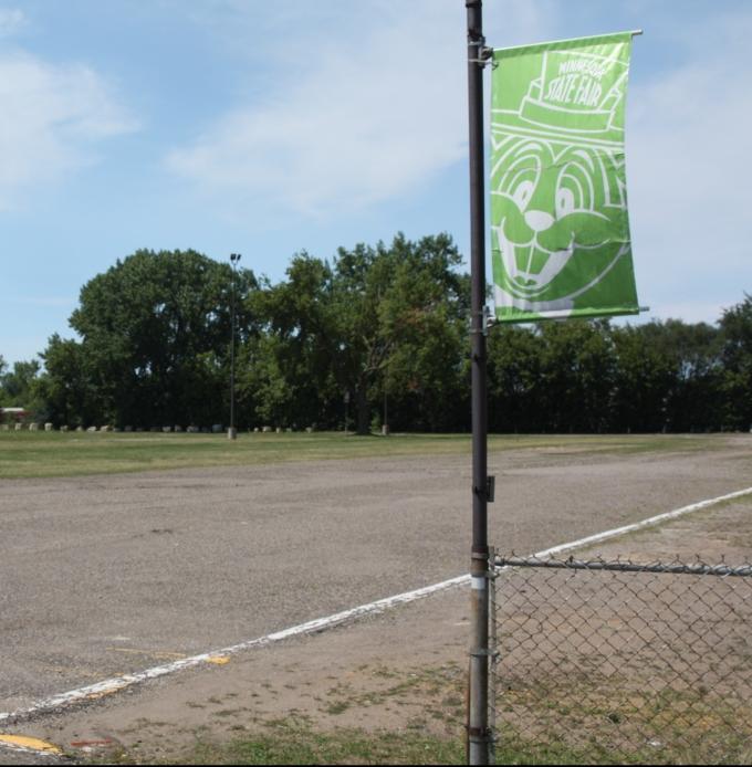 Another Fair banner oversees an parking lot.