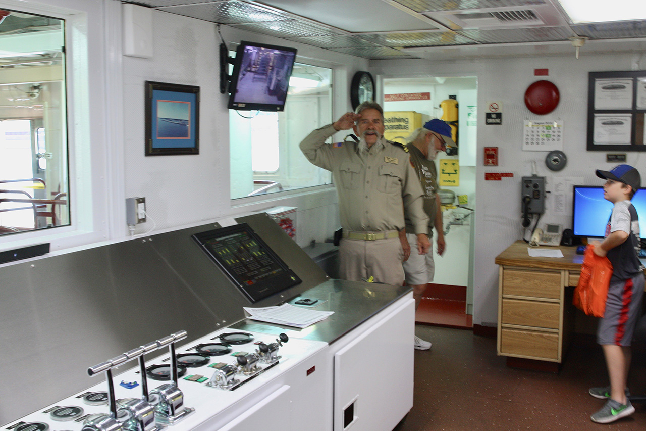 Assistant Engineer W.D. Mohon gives a salute in the engineering control room.