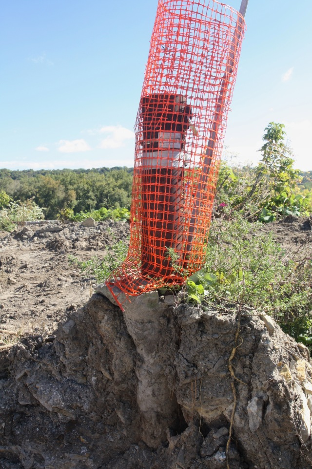 One of the remaining Minnesota Department of Health soil monitoring wells is wrapped in plastic DayGlo Blaze Orange fence to in an effort to protect it from bulldozers and loaders.