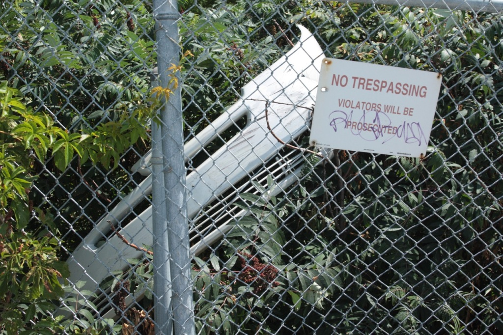 This discarded car bumper leaning on the No Trespassing sign struck me as funny.