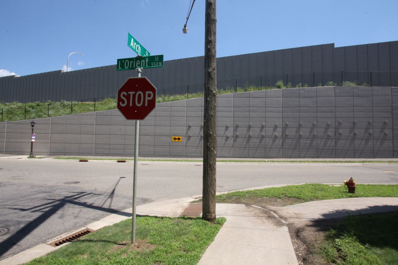 Arch Street meets L'Orient Street on the east. The large wall blocks the sound and visual bustle of I-35E.