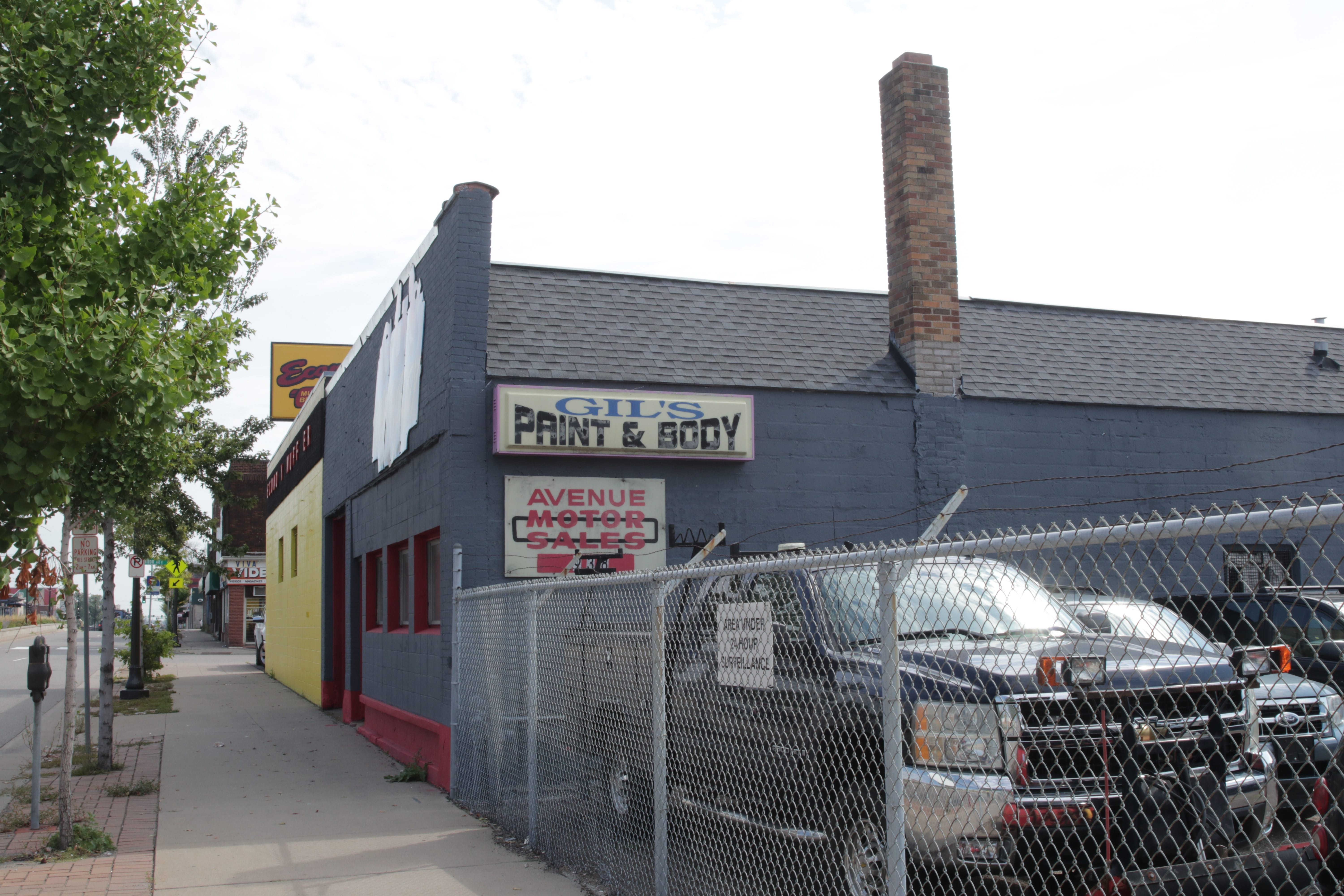 A shared parking lot separate Avenue Motor Sales and Gil's Paint and Auto Body.