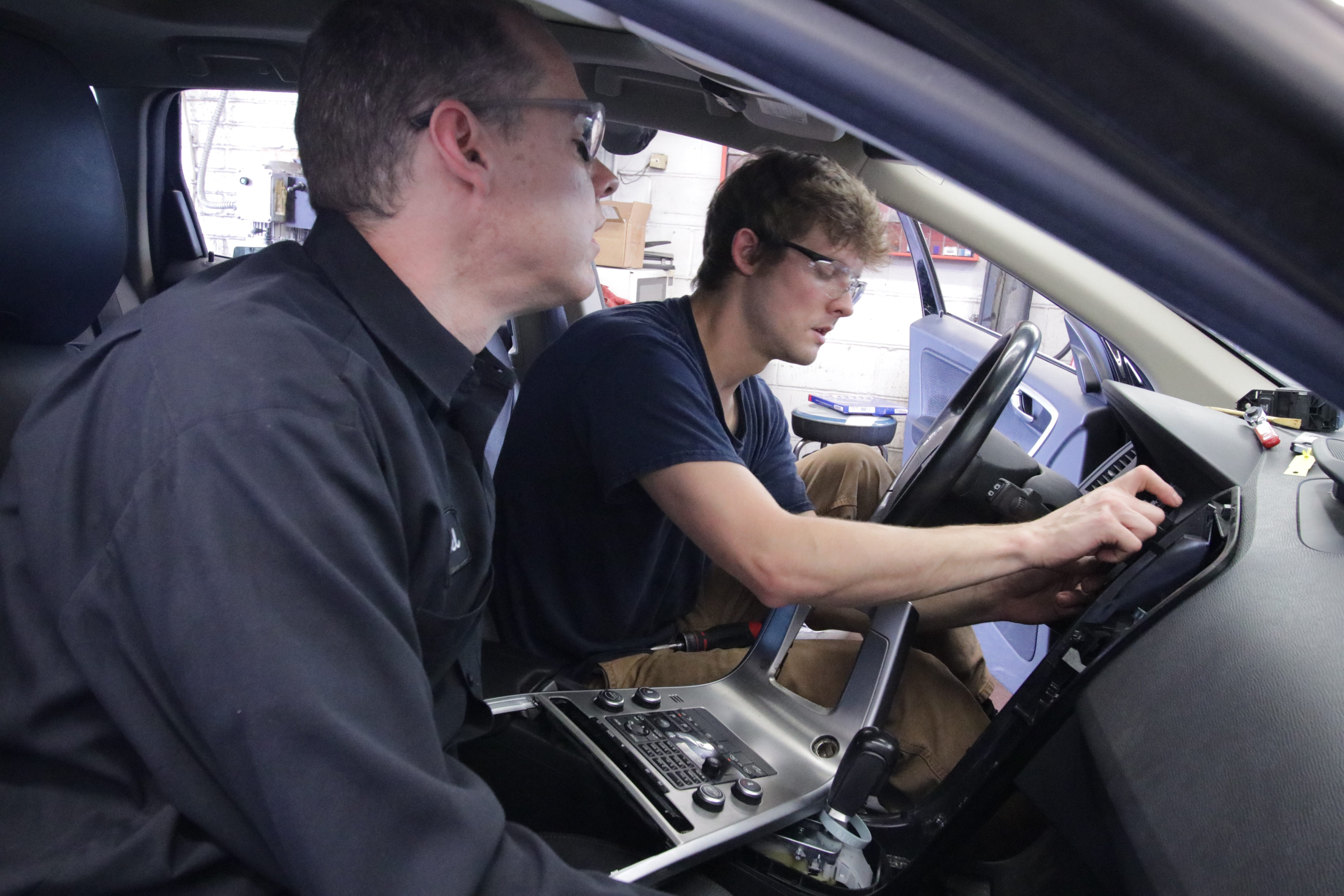 Mike Glasgow Jr., the third generation to work at Glasgow Automotive, works with another mechanic to make repairs behind the dashboard.