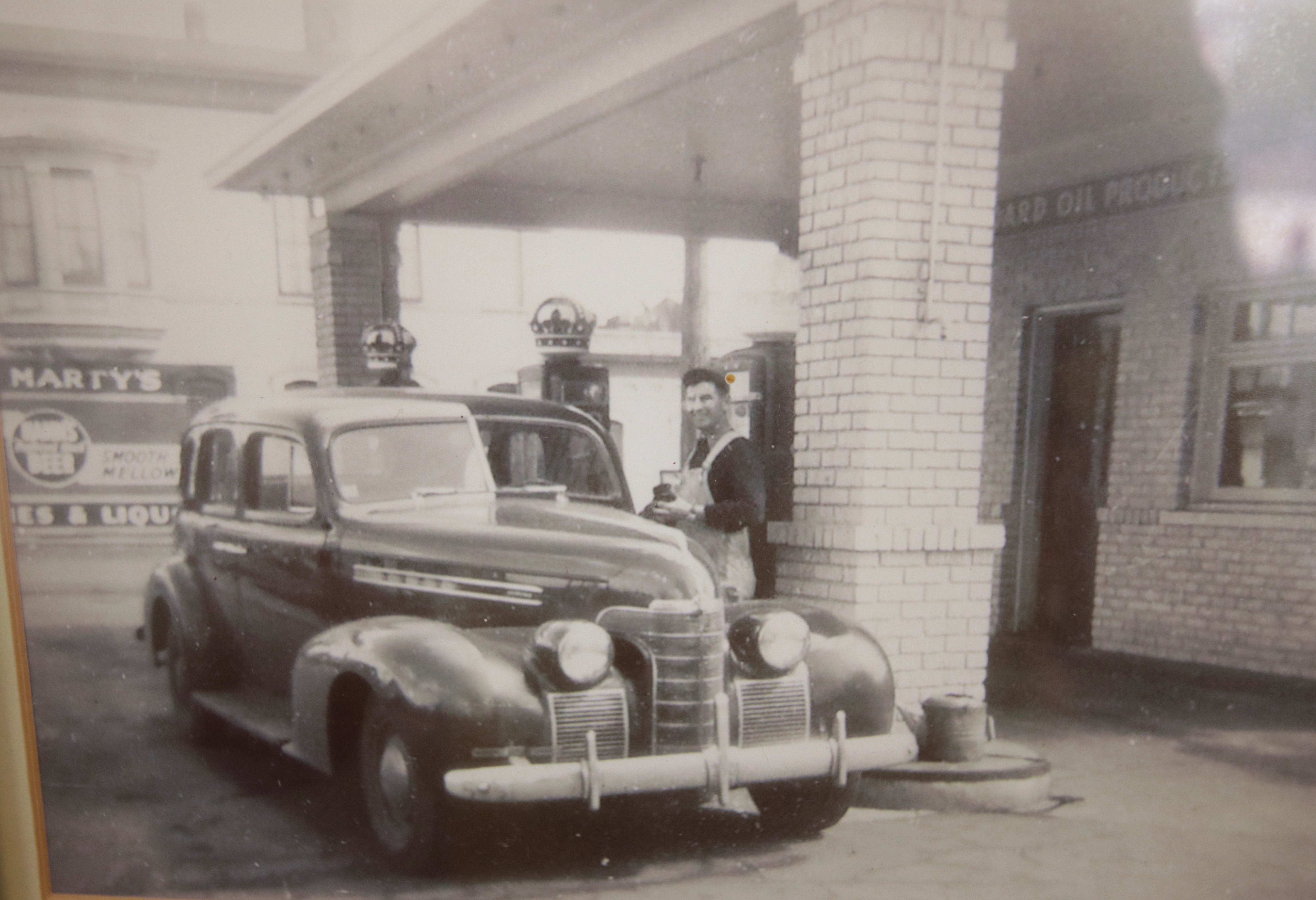 This shot of the Standard Oil gas station, later Glasgow Automotive, at 740 West University is displayed on an office wall. In the background you can see the Marty's Bar sign on the exterior wall of the establishment.