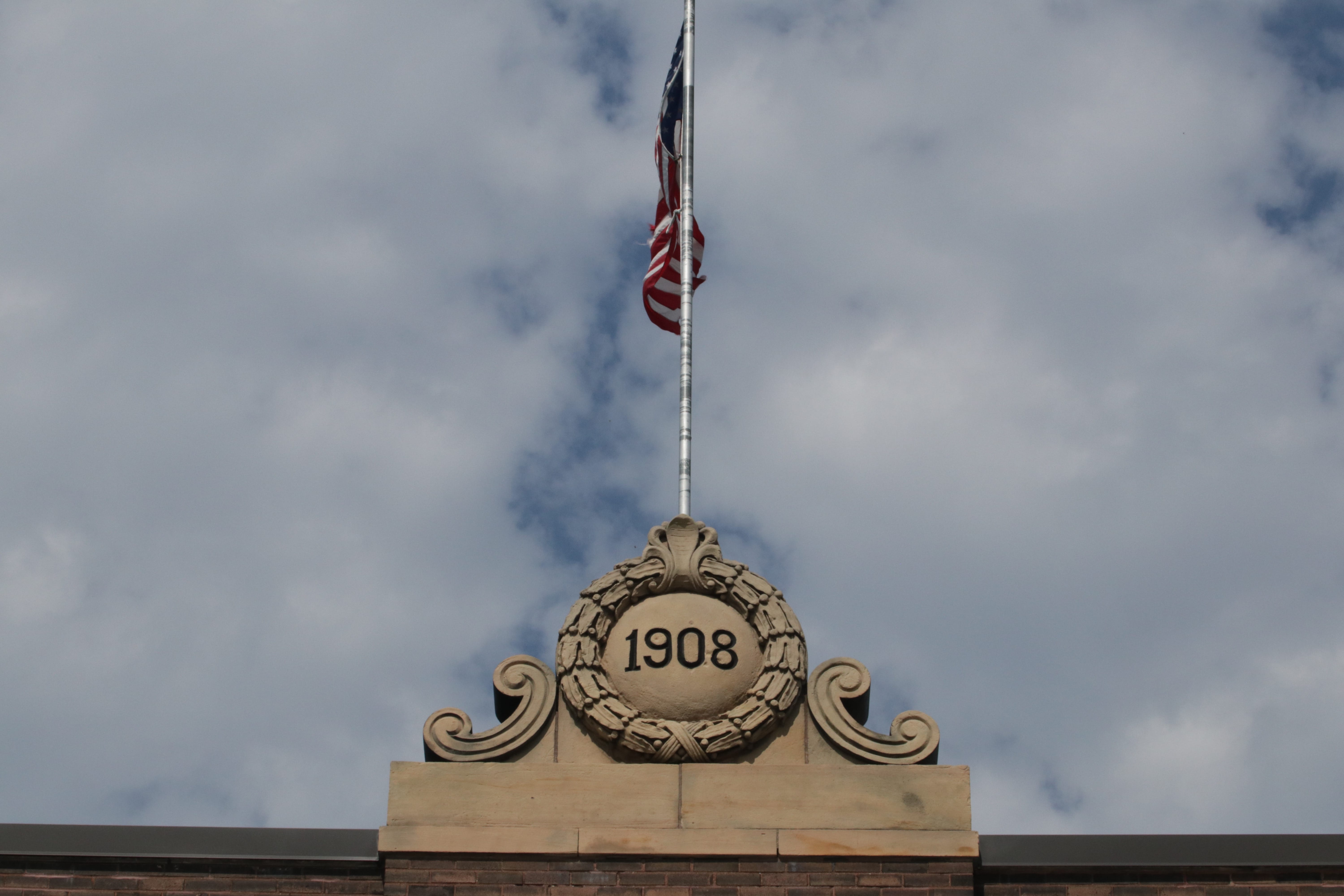 The pediment displaying the year Station 18 opened also holds the flag pole.